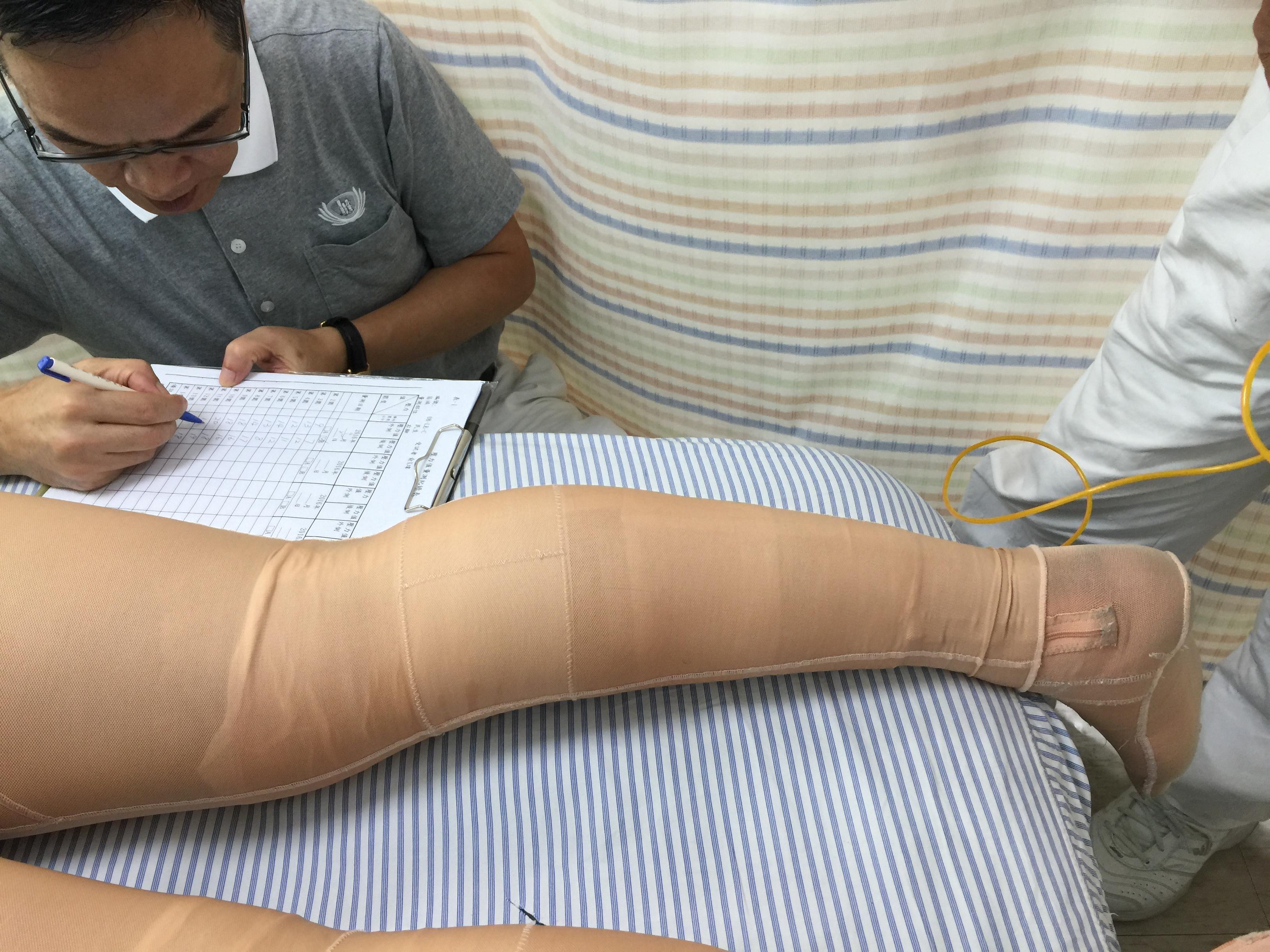 慈濟基金會志工協助量測傷友穿戴高彈力機能透氣肢體壓力服之壓力值