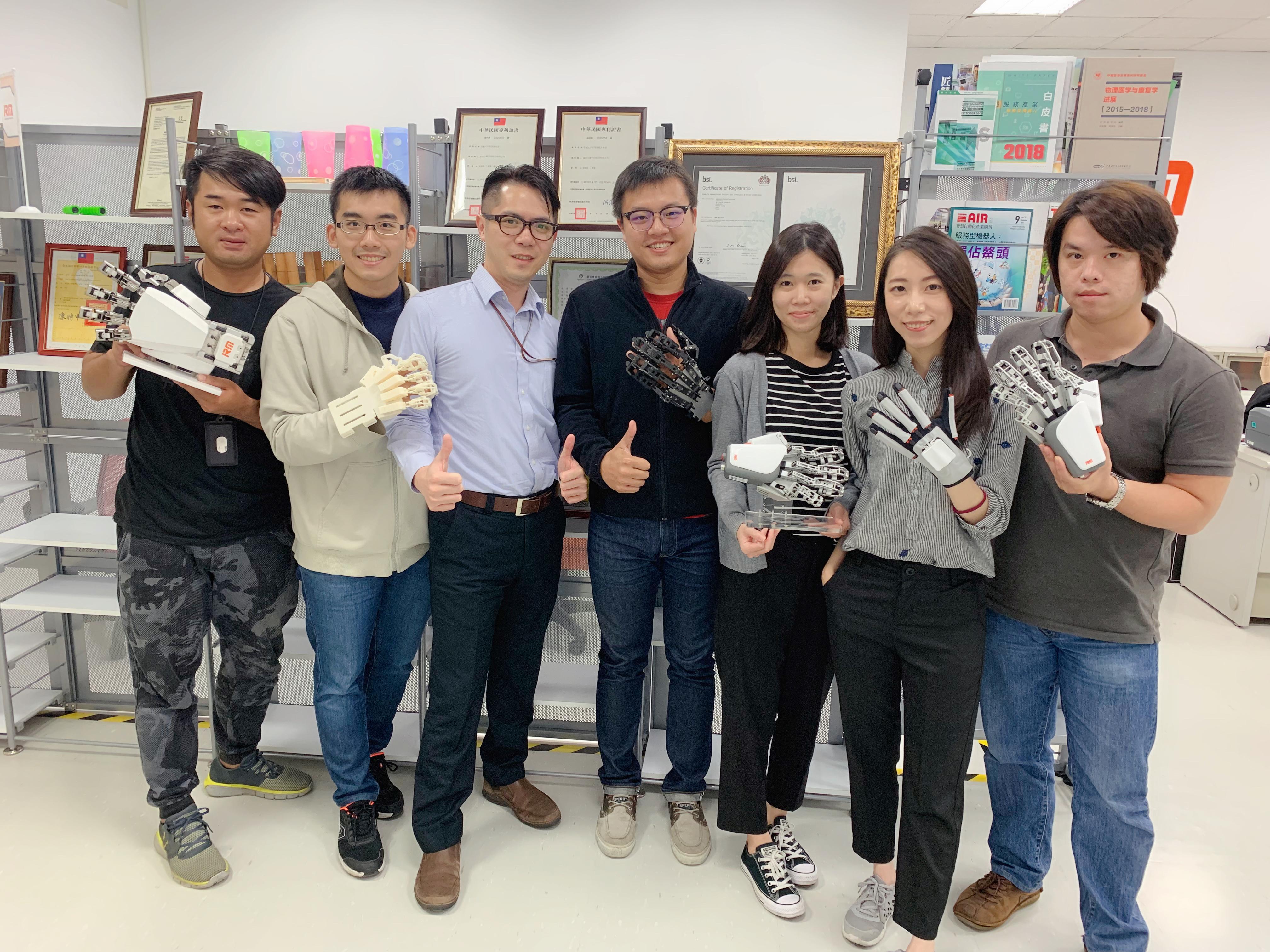 團隊照,手中產品是依序研發歷程(由左至右)